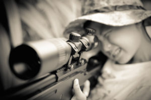 A young child takes aim with a rifle.